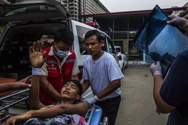 A protestor who was shot in the chest with live ammunition arrives at a hospital for treatment.