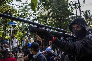 A man aims a home made weapon as anti-coup protestors and frontline defenders get ready for the expected crack down by the security forces in Tharketa township.