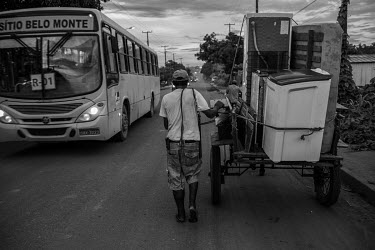 A man moves his family's furniture in a cart after struggling with the rent for their house after prices skyrocketed, especially for housing and food, as the urban population of Altamira increased fro...