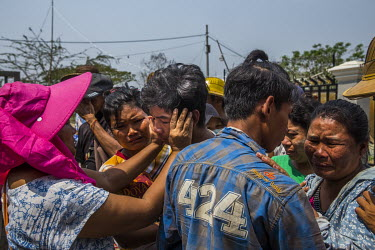 Family members mourn as people take away the dead body of U Win Myint (46) who was shot in the chest when security forces fired live rounds at anti-coup protestors earlier in the morning in the distri...