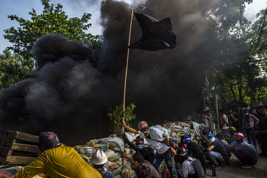 Thick smoke rises ahead of a barrier erected by frontline defenders, flying their black flag, and anti-coup protestors as they clash with security forces in Tharketa township.