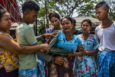 Family members help as the mother of Aung Zin Myint, a 20 year old student protestor who was shot in the chest and arm and died, when the security forces fired on anti-coup protestors earlier in the m...