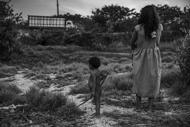 An indigenous Piraha woman and child watch a cattle truck passing on the Trans-Amazonian Highway near their camp on the banks of the Maici river.