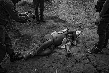 Police officers photograph and examine the body of a man killed in rural Altamira. The police have laid out bank notes found on the dead man which they say indicates he was executed and not killed dur...