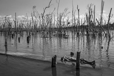 A boy rests on the banks of the Xingu River in Paratizao, a river dweller community located near the dam of Belo Monte. The place is surrounded by great toothpick-like patches of dead trees, formed af...