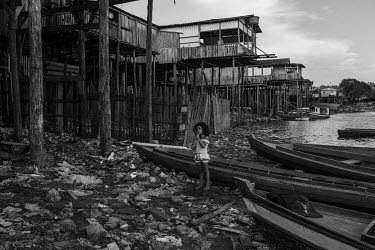A girl waits to get into a canoe on the rubbish strewn banks of the Xingu River which is lined by stilt-houses and a wooden pier.