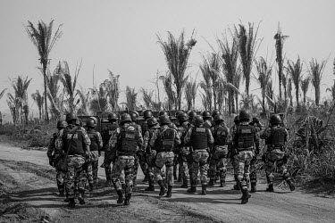 Riot police walk down a dirt road inside the Bom Futuro National Forest to remove invaders who had set up a camp with about 200 shacks inside the reserve. In 2019, Bom Futuro lost 874 hectares of fore...