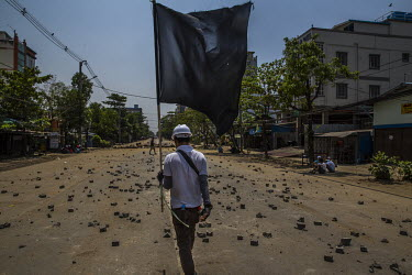 An anti-coup protestor carries a black flag, a symbol of the more militant protestors, as he walks on a road strewn with broken bricks scattered to try and block the security forces from entering Thar...