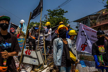 Anti-coup protestors raise a black flag over a barricade erected in Tharketa township ahead of a crack down by the security forces.