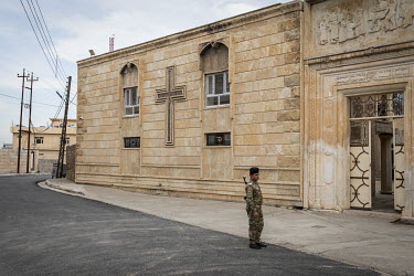 A policeman on guard in front of the Mart Shmouni (Shmoni) Syriac Orthodox Church which was burned and badly damaged by ISIS terrorists during their occupation of Bartella.   Prior to being overrun by...