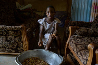 Bedine (10), a housekeeper for a local family, shells peanuts. Its not unusual for the families of young girls to send them to work to wealthier families, to help with household chores.