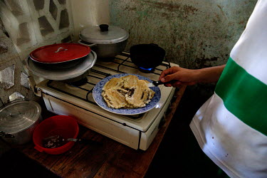 Farides Farid Cantillo Silva prepares patacones, fried green bananas or plantains depending on availablity, for lunch at her home in Cienaga.