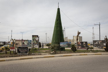 A Christmas tree at the entrance to Bartella standing amidst posters depicting Shiite martyrs, including Abu Mahdi al-Muhandis, the former head of the Iraqi Popular Mobilisation Forces, who was killed...