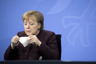 German Chancellor Angela Merkel puts on a face mask after speaking to the media at the Chancellery Office following a telephone conference call with leaders of the Federal states to discuss COVID-19 r...
