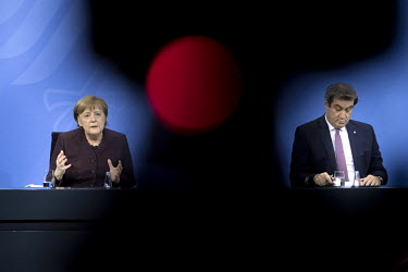 Chancellor Angela Merkel and Markus Soeder, Bavaria's State Premier, speak to the media at the Chancellery Office following a telephone conference call with leaders of the Federal states to discuss CO...