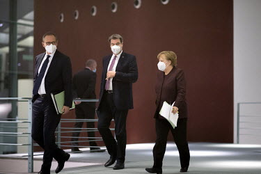 Michael Mueller, Mayor of Berlin, Markus Soeder, Bavaria's State Premier, and German Chancellor Angela Merkel (f.l.t.r.) at the Chancellery Office following a telephone conference call with leaders of...