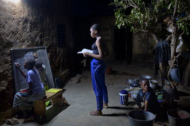 Rachel (left, sitting) studies at the home of a classmate who has an electric light at her house as she is from a poor family who have no electricity at home.