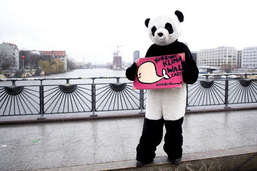 An environmental activist from WWF (World Wide Fund for Nature) dressed in a panda costume holds a sign on the closed Oberbaum Bridge during a protest calling for a 'Global Day of Climate Action' unde...