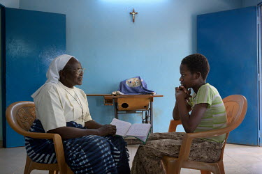 The mother superior, Sister Veronique talks with Abibou (13), who fled a child marriage, at the Foyer Sainte Maria de Goretti which since 1951 has been welcoming young girls fleeing early and forced m...