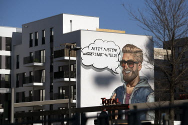 An advertisment reads: 'Now For Rent' ('Jetzt Mieten') on the side of a newly built apartment block on Heidestrasse. The project is part of the 'Wasserstadt Mitte' (Water City Central) development by...