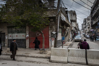 People walk past a shuttered shop front painted with the flags of Turkey and the Free Syrian Army in downtown Afrin.