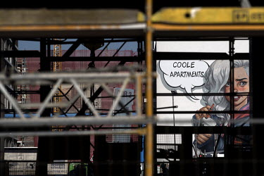 An advertisment reads: 'Coole Apartments' on the side of a newly built apartment block on Heidestrasse. The project is part of the 'Wasserstadt Mitte' (Water City Central) development by Adler Real Es...
