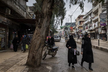 People walking through the heavily-secured market area in downtown Afrin.