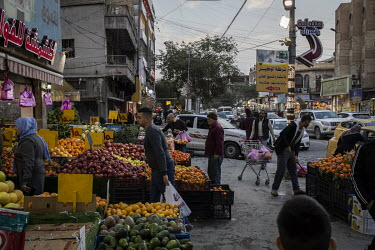 Customers choose produce at a fruit and vegetable shop in the Karada neighbourhood. The government's restrictions to control the spread of COVID-19 are loosely implemented and many people seem unafrai...