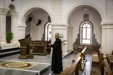 Father Banham Lalo prays in the new Mar Goris Syriac-Catholic church (St George) which has been rebuilt following its destruction by Islamic State during their occupation of the town.   Prior to being...