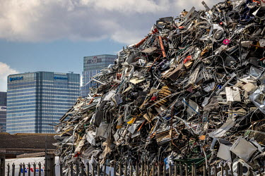 A scrap metal yard in the Lea Valley with high rise towers in Canary Wharf containing the headquarters of Barclays and Citigroup rising behind. The huge mound of ferrous scrap was growing because the...
