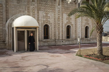 Father Banham Lalo stands in the side entrance to the new Mar Goris Syriac-Catholic church (St George) which has been rebuilt following its destruction by Islamic State during their occupation of the...