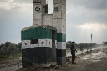 Turkish-backed Syrian security forces man a checkpoint on the road between Afrin and the Turkish border.