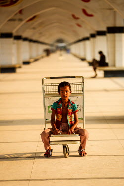A homeless boy sitting on a luggage trolly at at Kamalapur Railway Station (officially known as Dhaka railway station).