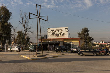 A billboard depicting the late Iranian cleric Ayatollah Khomeini alongside Iraqi Shiite martyrs at the entrance to Bartella where a large Christain cross stands on a road island.   Prior to being over...