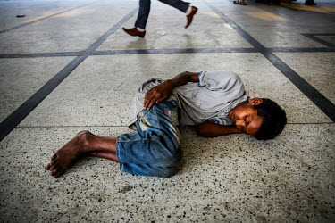 A homeless boy sleeping on the concourse at Kamalapur Railway Station (officially known as Dhaka railway station).