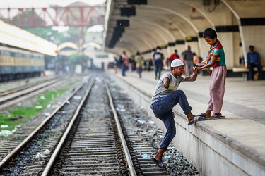 A boy helps his disabled companion on to a platform at Kamalapur Railway Station (officially known as Dhaka railway station).