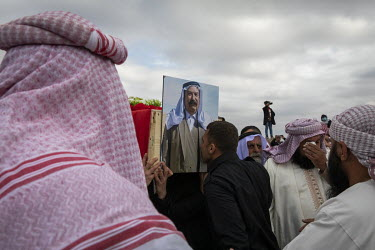 A relative kisses the photograph of a Yazidi man displayed on one of the coffins carried during a funeral procession for 103 Yazidis murdered by ISIS in the village of Kocho in 2014. Having been exhum...