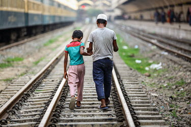 A boy leads a disabled youth along the tracks at Kamalapur Railway Station (officially known as Dhaka railway station).