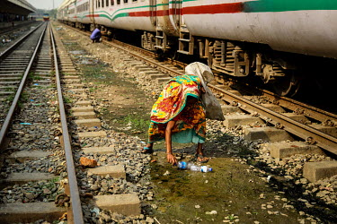 A woman collecting recylable waste at Kamalapur Railway Station (officially known as Dhaka railway station).