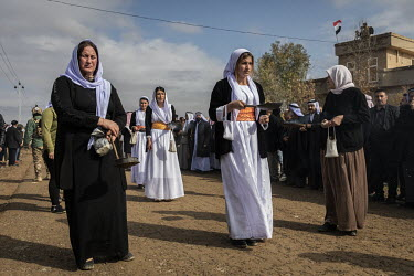 Yazidi women burn incense as they walk ahead of the funeral procession for the 103 Yazidis from the village of Kocho killed by ISIS in 2014. Having been exhumed from the mass graves where they were du...
