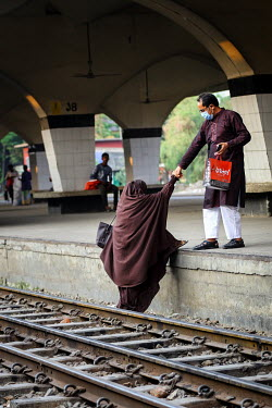 A man helps a woman on to the platform after crossing the tracks at Kamalapur Railway Station (officially known as Dhaka railway station).
