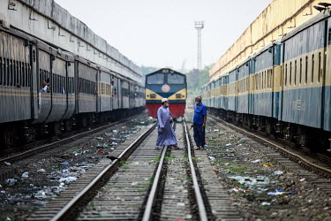 Two men casually cross the tracks in front of a train at Kamalapur Railway Station (officially known as Dhaka railway station).