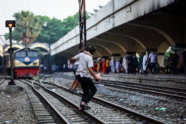 A man carries a boy across the tracks at Kamalapur Railway Station (officially known as Dhaka railway station).