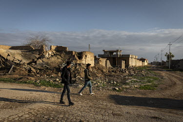 Two teenage youths walk through the abandoned Yazidi village of Kocho which still lies in ruins more than four years after it was liberated from ISIS rule.