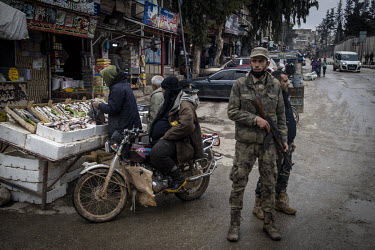 Turkish-backed Syrian security forces on guard beside a fish stall in the heavily-secured market area of downtown Afrin.