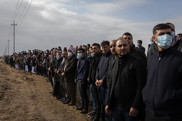 Yazidi men line up along the side of the road, awaiting the funerary procession for the 103 Kocho residents murdered by ISIS. Having been exhumed from the mass graves where they were dumped by ISIS in...