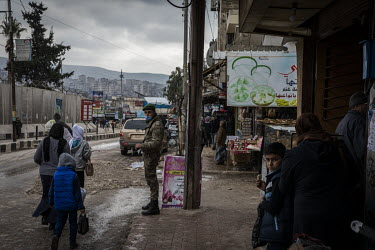 A guard standing outside a parade of shops opposite the Turkish administrative building in the heavily-secured market area of downtown Afrin.