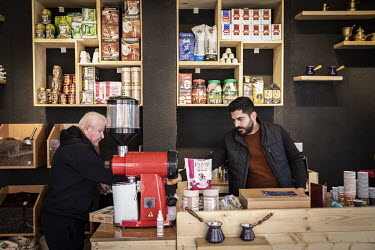 Karam Rafael serves a customer in his newly opened coffee shop.   Prior to being overrun by ISIS in August 2014 the town was majority Christian but following its liberation, on 20 October 2016 by Iraq...