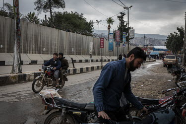 Two men ride on a motorcycle past the blast walls of Turkish administrative building in the heavily-secured market area of downtown Afrin.