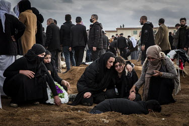 Yazidi women comfort each other as the family bury the remains of a relative, one of 103 people from the village murdered by ISIS in 2014. Having been exhumed from the mass graves where they were dump...